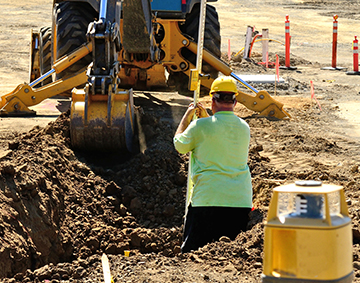 Worker in ditch helping set helical anchors