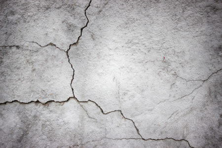 cracked concrete wall covered with gray cement texture